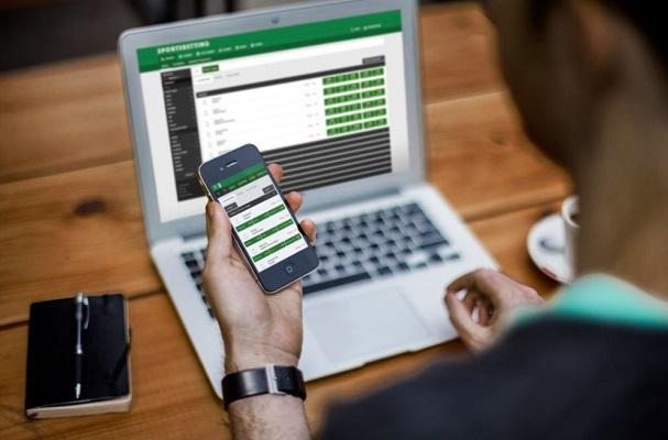 Un hombre apuesta por su teléfono y su computadora portátil.